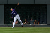 Right fielder Carlos Gonzalez of the Colorado Rockies throws to second base to catch Chris Johnson of the Atlanta Braves trying to stretch his single...