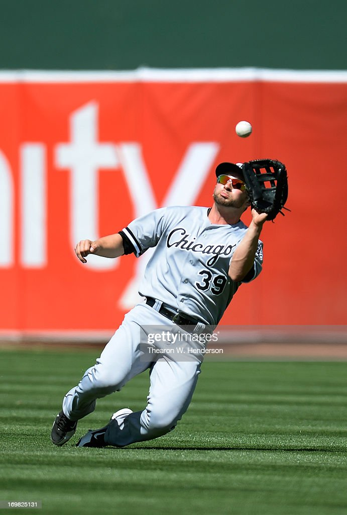 Right Fielder <a gi-track='captionPersonalityLinkClicked' href=/galleries/search?phrase=Casper+Wells&family=editorial&specificpeople=5747458 ng-click='$event.stopPropagation()'>Casper Wells</a> #39 of the Chicago White Sox goes into a slide to catch a shallow fly ball taking a hit away from Chris Young #25 of the Oakland Athletics in the seventh inning at O.co Coliseum on June 2, 2013 in Oakland, California.