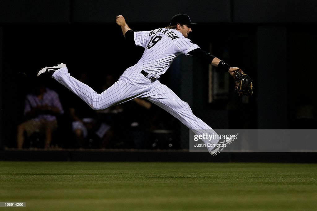 Right fielder Charlie Blackmon #19 of the Colorado Rockies stretches out after making a catch on the run for the second out of the seventh inning against the San Francisco Giants at Coors Field on May 16, 2013 in Denver, Colorado. The Giants defeated the Rockies 8-6.