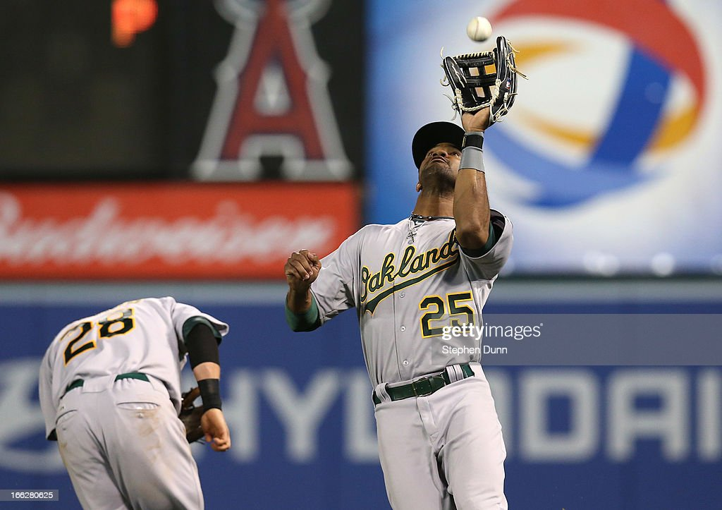 Right fielder Chris Young #25 of the Oakland Athletics runs down a fly ball hit by Brendan Harris of the Los Angeles Angels of Anaheim as second baseman Eric Sogard #28 ducks out of the way at Angel Stadium of Anaheim on April 10, 2013 in Anaheim, California.