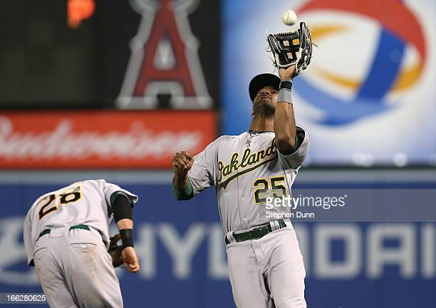 Right fielder Chris Young of the Oakland Athletics runs down a fly ball hit by Brendan Harris of the Los Angeles Angels of Anaheim as second baseman...