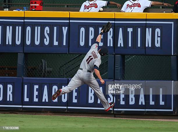 Right fielder Drew Stubbs of the Cleveland Indians jumps and just misses a fly ball hit by Elliot Johnson of the Atlanta Braves during the game at...