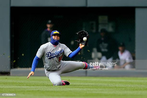 Right fielder Enrique Hernandez of the Los Angeles Dodgers makes a sliding catch for the second out of the sixth inning against the Colorado Rockies...