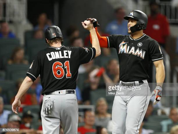 Right fielder Giancarlo Stanton of the Miami Marlins celebrates with pitcher Adam Confey after Stanton's 2run home run in the sixth inning during the...