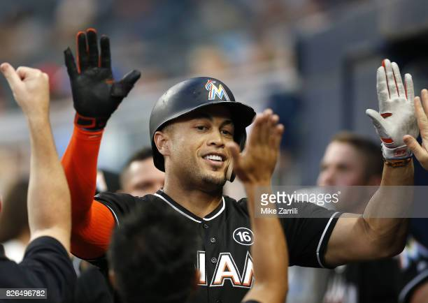 Right fielder Giancarlo Stanton of the Miami Marlins is congratulated in the dugout after hitting a home run in the fourth inning during the game...