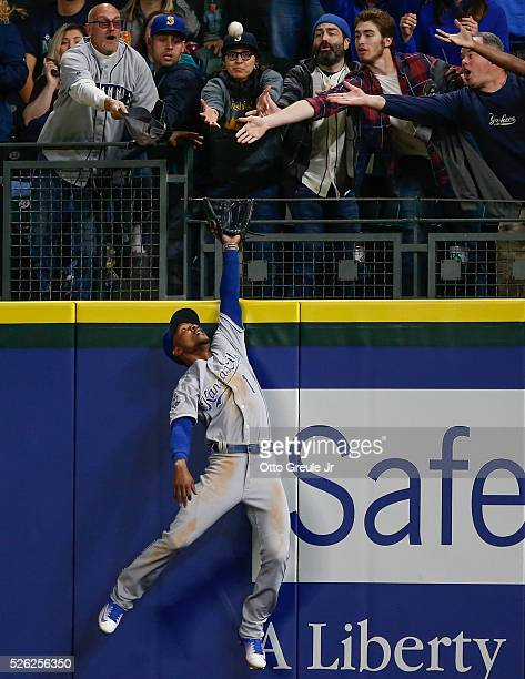 Right fielder Jarrod Dyson of the Kansas City Royals leaps at the wall for a home run off the bat of Seth Smith of the Seattle Mariners in the sixth...