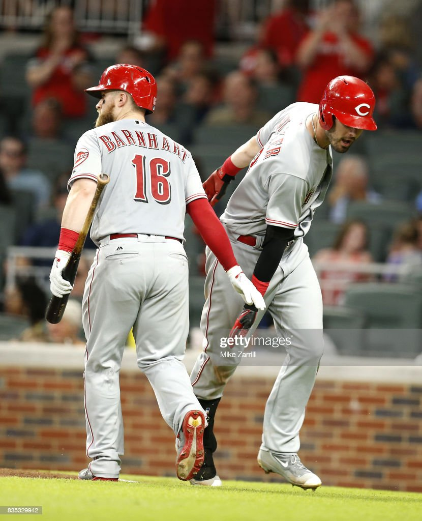Right fielder Jesse Winker #33 of the Cincinnati Reds is congratulated by teammate and catcher Tucker Barnhart #16 after Winker's solo home run in the sixth inning during the game against the Atlanta Braves at SunTrust Park on August 18, 2017 in Atlanta, Georgia.