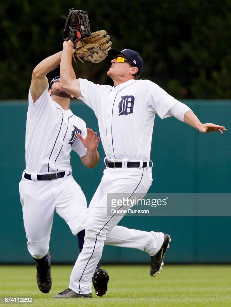 Right fielder Jim Adduci of the Detroit Tigers beats center fielder Tyler Collins of the Detroit Tigers to a fly ball hit by Nelson Cruz of the...