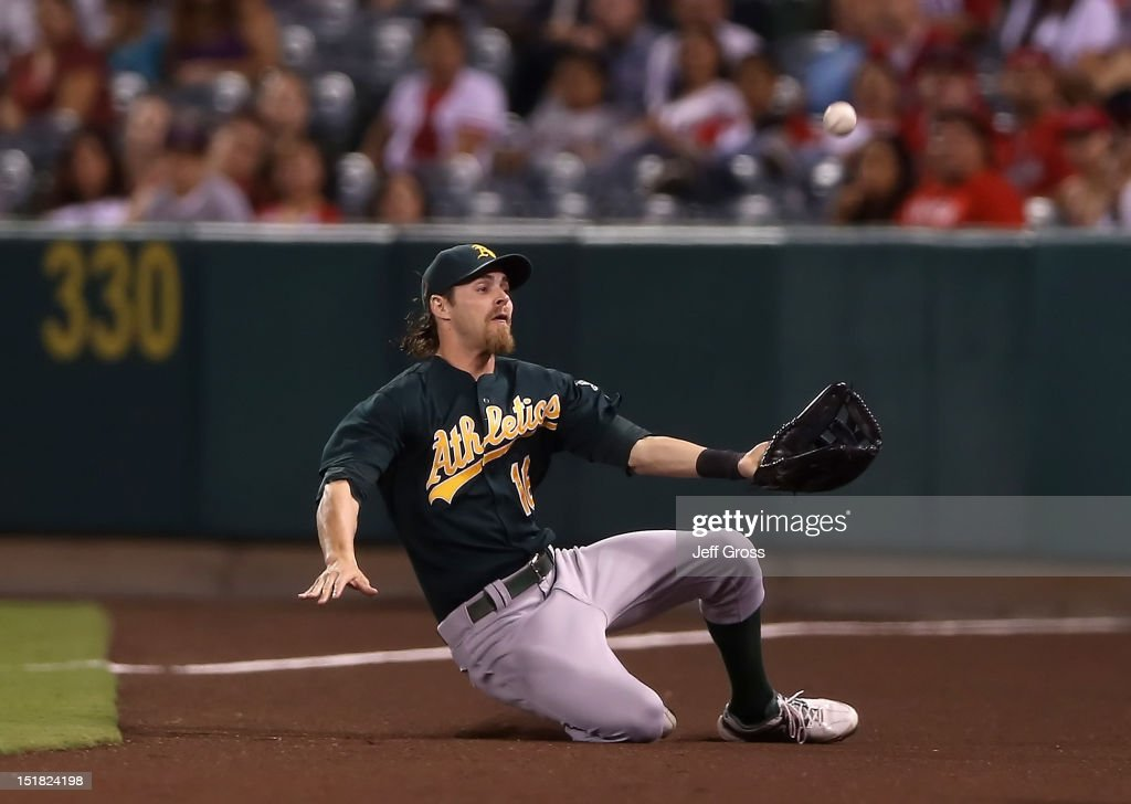 Right fielder <a gi-track='captionPersonalityLinkClicked' href=/galleries/search?phrase=Josh+Reddick&family=editorial&specificpeople=5746348 ng-click='$event.stopPropagation()'>Josh Reddick</a> #18 of the Oakland Athletics makes a sliding catch in foul territory on a ball hit by Albert Pujols of the Los Angeles Angels of Anaheim in the second inning at Angel Stadium of Anaheim on September 11, 2012 in Anaheim, California.