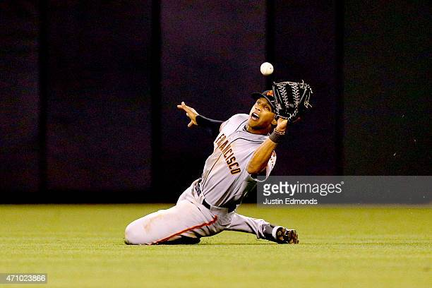 Right fielder Justin Maxwell of the San Francisco Giants makes a sliding catch to end the eighth inning against the Colorado Rockies at Coors Field...