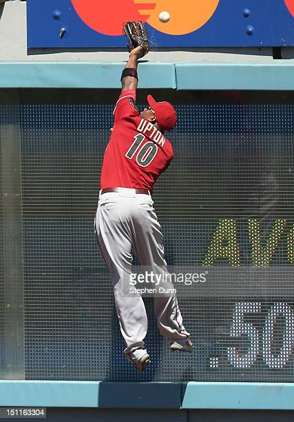 Right fielder Justin Upton of the Arizona Diamondbacks can't catch a home run ball hit by Andre Ethier of the Los Angeles Dodgers in the second...