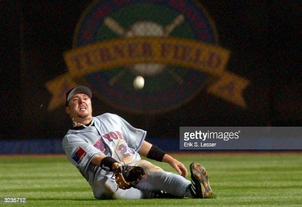 Right fielder Karim Garcia of the New York Mets slides attempting to catch a fly ball from Marcus Giles of the Atlanta Braves in the 8th inning on...