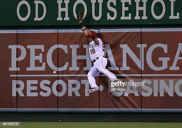 Right fielder Kole Calhoun of the Los Angeles Angels of Anaheim can't make the catch on a ball hit by Dustin Ackley of the Seattle Mariners in the...