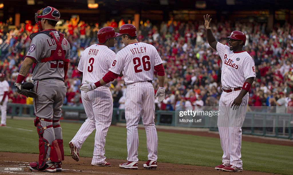 Right fielder Marlon Byrd #3 of the Philadelphia Phillies is greeted by second baseman Chase Utley #26 and first baseman Ryan Howard #6 after hitting a three run home run in the first inning against the Washington Nationals on May 2, 2014 at Citizens Bank Park in Philadelphia, Pennsylvania.