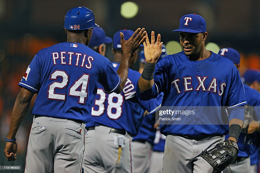 Right fielder <a gi-track='captionPersonalityLinkClicked' href=/galleries/search?phrase=Nelson+Cruz&family=editorial&specificpeople=235459 ng-click='$event.stopPropagation()'>Nelson Cruz</a> #17 of the Texas Rangers celebrates with third base coach Gary Pettis #24 after defeating the Baltimore Orioles at Oriole Park at Camden Yards on July 9, 2013 in Baltimore, Maryland. The Texas Rangers won, 8-4.