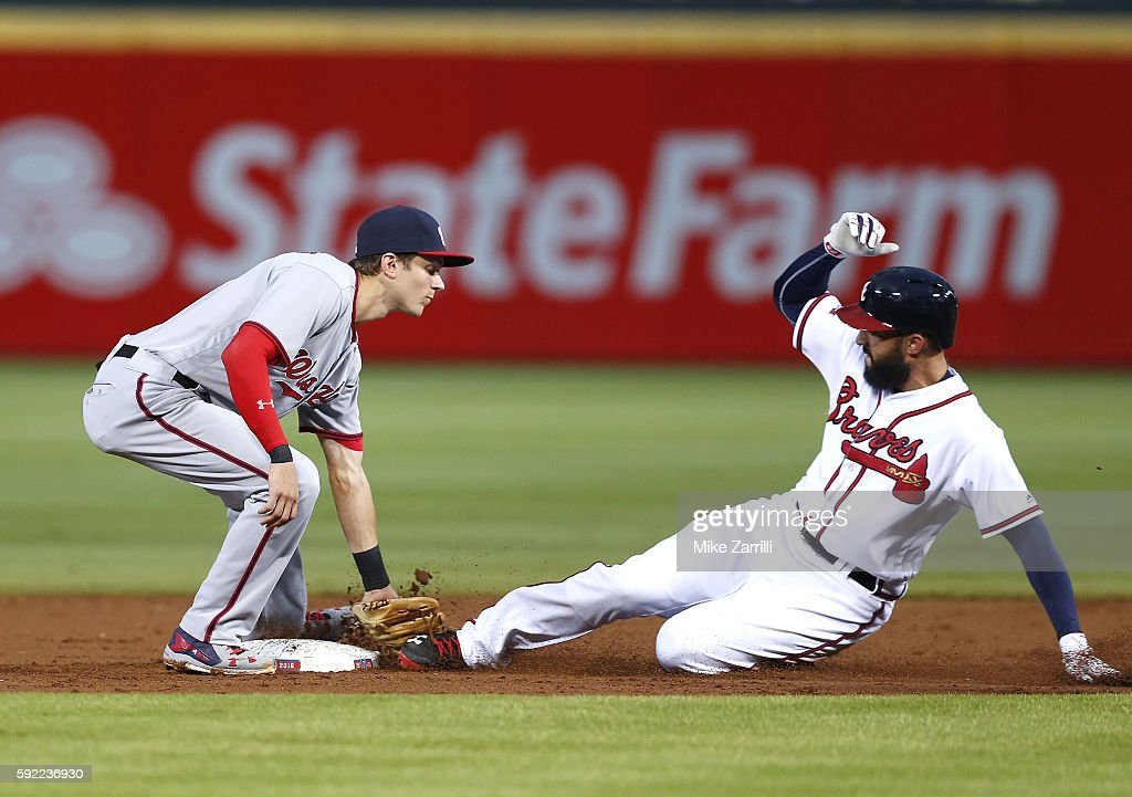 Right fielder Nick Markakis of the Atlanta Braves is tagged out during a stolen base attempt by second baseman Trea Turner of the Washington...