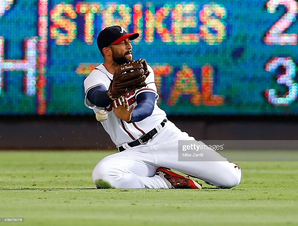 Right fielder Nick Markakis of the Atlanta Braves slides in front of a ball hit by outfielder Justin Upton of the San Diego Padres in the third...