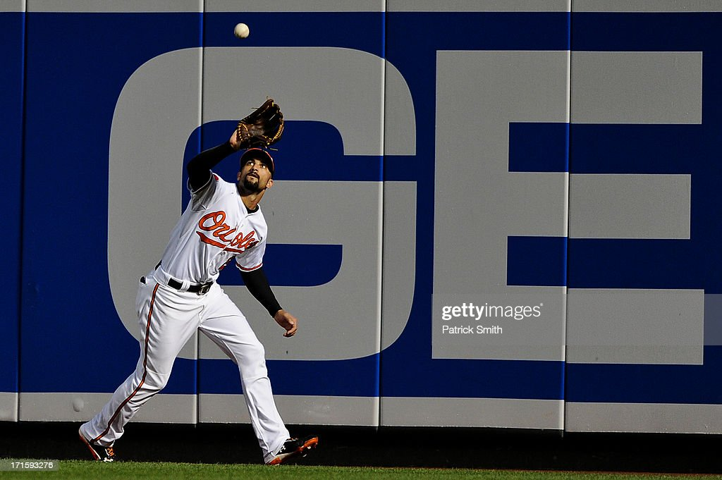 Right fielder <a gi-track='captionPersonalityLinkClicked' href=/galleries/search?phrase=Nick+Markakis&family=editorial&specificpeople=614708 ng-click='$event.stopPropagation()'>Nick Markakis</a> #21 of the Baltimore Orioles catches a hit by Yan Gomes #10 of the Cleveland Indians (not pictured) in the third inning at Oriole Park at Camden Yards on June 26, 2013 in Baltimore, Maryland.