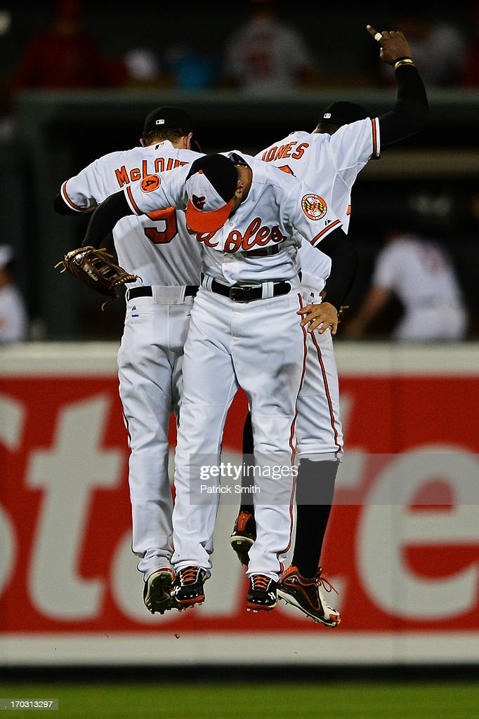Right fielder Nick Markakis #21 of the Baltimore Orioles (center) celebrates with teammates Nate McLouth #9 (left) and Adam Jones #10 after defeating the Los Angeles Angels of Anaheim at Oriole Park at Camden Yards on June 10, 2013 in Baltimore, Maryland. The Baltimore Orioles won, 4-3.