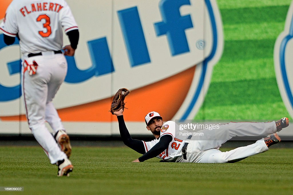 Right fielder <a gi-track='captionPersonalityLinkClicked' href=/galleries/search?phrase=Nick+Markakis&family=editorial&specificpeople=614708 ng-click='$event.stopPropagation()'>Nick Markakis</a> #21 of the Baltimore Orioles makes a catch for an out on Chad Tracy #18 of the Washington Nationals (not pictured) in the second inning during an interleague game at Oriole Park at Camden Yards on May 29, 2013 in Baltimore, Maryland.