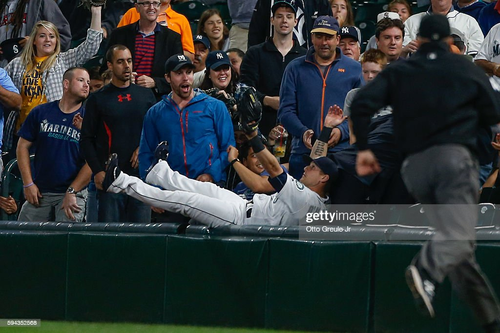 Right fielder Shawn O'Malley of the Seattle Mariners emerges from the stands after diving to catch a fly ball off the bat of Tyler Austin of the New...