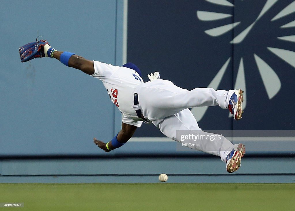 Right fielder <a gi-track='captionPersonalityLinkClicked' href=/galleries/search?phrase=Yasiel+Puig&family=editorial&specificpeople=10484087 ng-click='$event.stopPropagation()'>Yasiel Puig</a> #66 of the Los Angeles Dodgers dives but can't make the catch on a ball hit by Marlon Byrd of the Philadelphia Phillies in the fifth inning at Dodger Stadium on April 24, 2014 in Los Angeles, California.