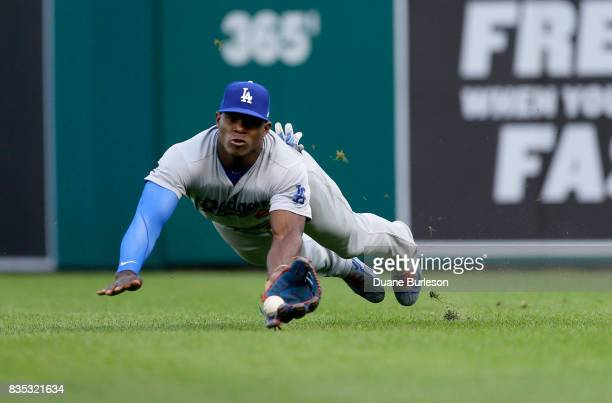 Right fielder Yasiel Puig of the Los Angeles Dodgers makes a diving catch on a fly ball hit by Nicholas Castellanos of the Detroit Tigers during the...