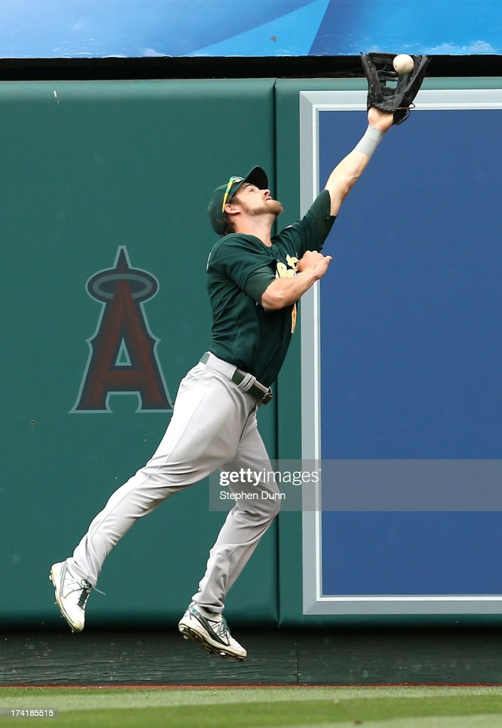 Right fielder<a gi-track='captionPersonalityLinkClicked' href=/galleries/search?phrase=Josh+Reddick&family=editorial&specificpeople=5746348 ng-click='$event.stopPropagation()'>Josh Reddick</a> #16 of the Oakland Athletics makes a leaping catch on a deep drive by Mike Trout #27 of the Los Angeles Angels of Anaheim in the fourth inning at Angel Stadium of Anaheim on July 21, 2013 in Anaheim, California.