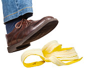 male right foot in jeans and brown shoe slips on a banana peel isolated on white background