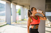 Female athlete drinking protein drink and listening to the music outdoors