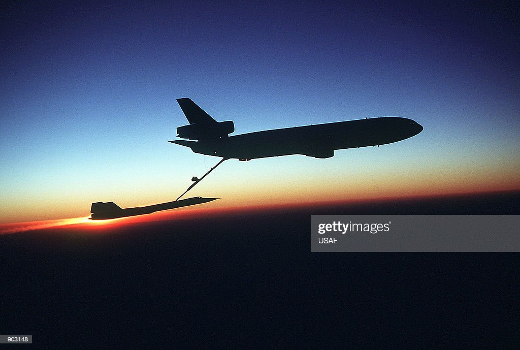 A right side view of a KC10 Extender aircraft refueling an SR71 Blackbird aircraft inflight during testing The Extender silhouetted against the...