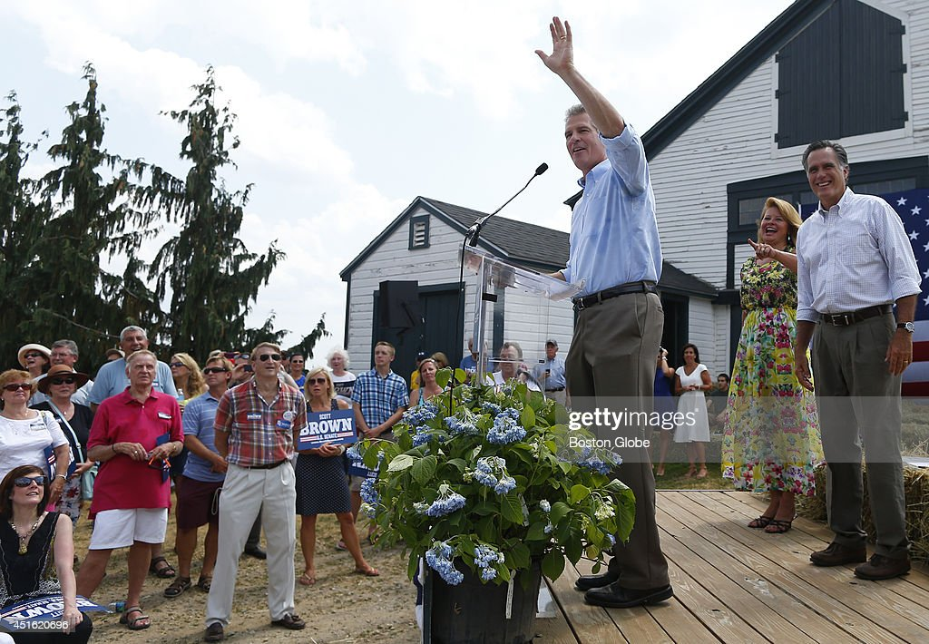 Right to left, Scott Brown addresses the crowd at Bittersweet Farm as his wife Gail Huff and Mitt Romney look on in Stratham, New Hampshire July 2, 2014.