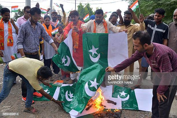 Right wing activists of Shiv Sena shout slogans as they burn Pakistani national flags during a demonstration on Pakistan's Independence Day in...