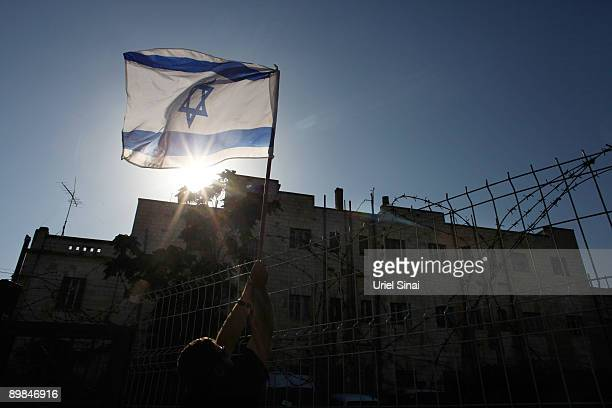 A right wing Israeli hangs an Israeli flag as US Republican presidential hopeful Mike Huckabee attends a function to support Jewish settlements...