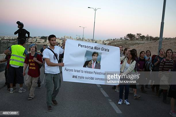 Right wing Israelis hold an anti US Secretary of State John Kerry banner as they march from the Jewish settlement of Maale Adumim to the...