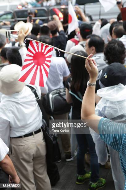 A right wing supporter waves rising sun flag to protest to the march of left wing supporters on August 15 2017 in Tokyo Japan Japan marks the 72nd...