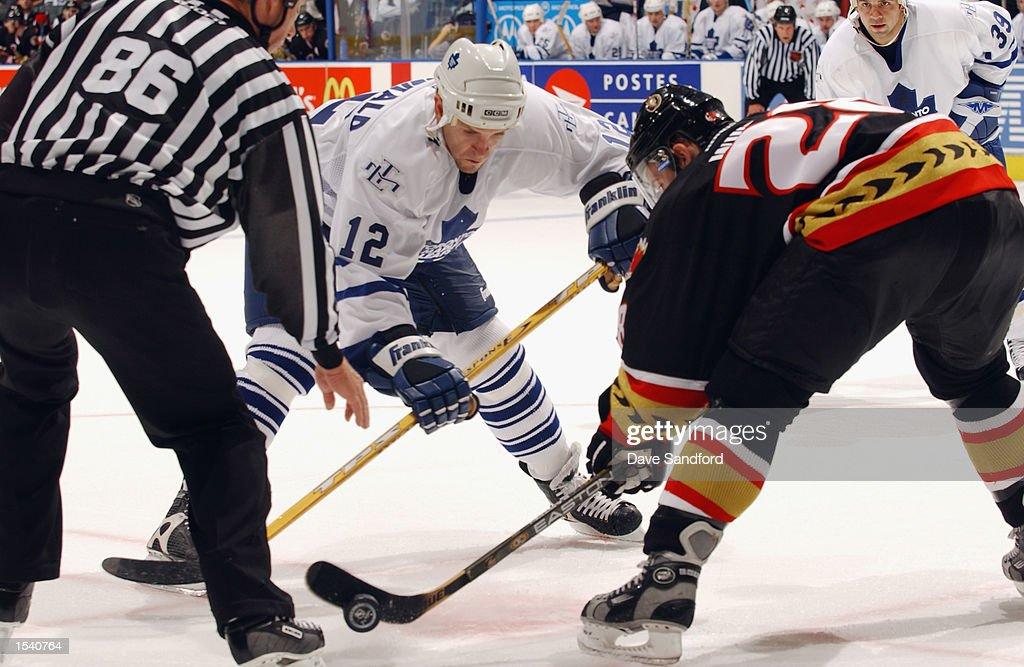 Right wing Tom Fitzgerald #12 of the Toronto Maple Leafs faces off against center Todd White #28 of the Ottawa Senators during the game on October 12, 2002 at Air Canada Centre in Toronto, Ontario, Canada.