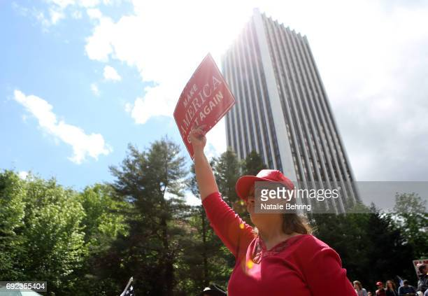 A right wing Trump supporter holds up a 'Make America Great Again' poster at a rally on June 4 2017 in Portland Oregon A protest dubbed 'Trump Free...