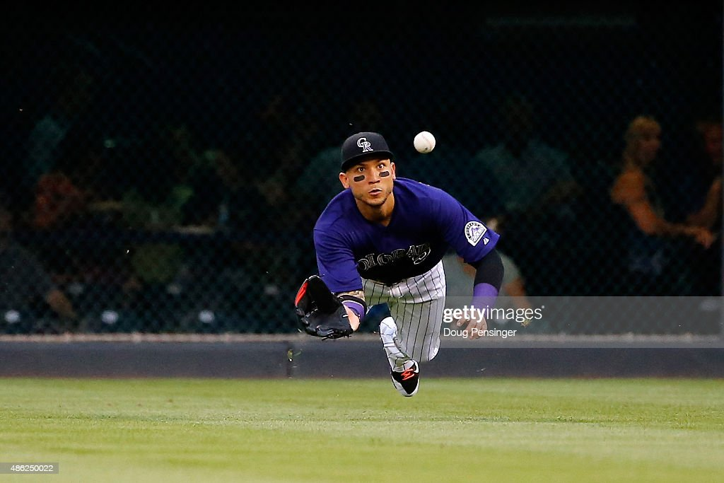 Rightfielder Carlos Gonzalez #5 of the Colorado Rockies makes a diving catch on a sacrifice fly by A.J. Pollock #11 of the Arizona Diamondbacks to score Ender Inciarte #5 of the Arizona Diamondbacks to take a 1-0 lead in the first inning at Coors Field on September 2, 2015 in Denver, Colorado.