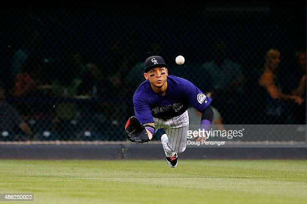 Rightfielder Carlos Gonzalez of the Colorado Rockies makes a diving catch on a sacrifice fly by AJ Pollock of the Arizona Diamondbacks to score Ender...