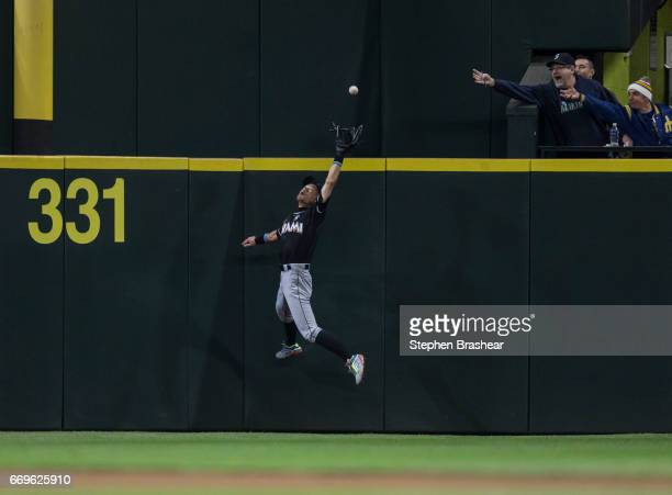 Rightfielder Ichiro Suzuki of the Miami Marlins catches a ball at the wall hit by Taylor Motter of the Seattle Mariners during the eighth inning of a...