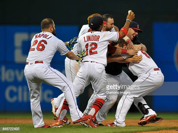 Rightfielder Lonnie Chisenhall of the Cleveland Indians is mobbed by designated hitter Mike Napoli shortstop Francisco Lindor thirdbaseman Jose...