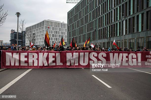 Rightwing activists hold a banner reading 'Merkel must go' as they gather to march in the city center and protest against German Chancellor Angela...