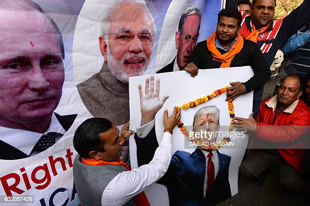 Rightwing activists of India's Hindu Sena party pose with a poster of Russian President Vladimir Putin Indian Prime Minister Narendra Modi and US...