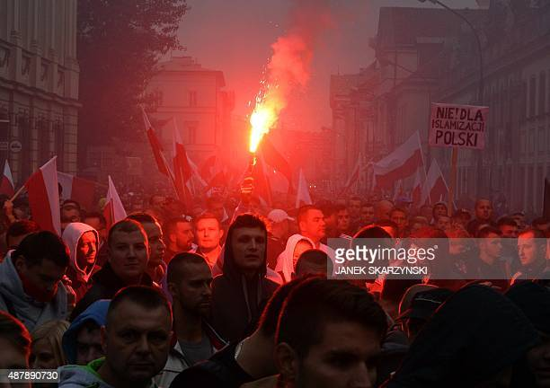 Rightwing demonstrators light fireworks during a protest against migrants in Warsaw on September 12 2015 Many of the nearly 5000 opponents chanted...