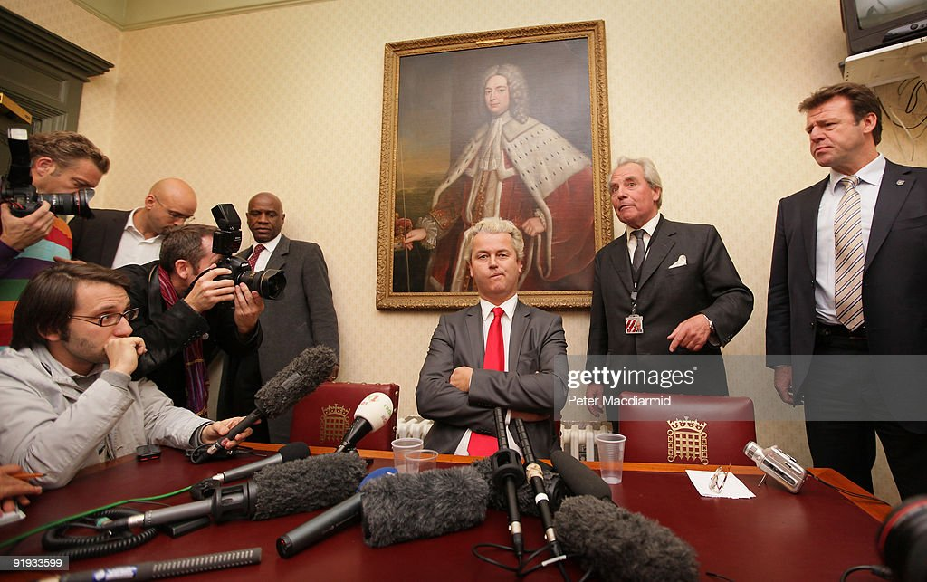 Right-wing Dutch MP Geert Wilders (C) is watched by Lord Pearson and a security official (R) as he speaks to reporters near Parliament on October 16, 2009 in London. Mr Wilders was allowed into the UK after he overturned a previous ban by the UK immigration authorities. About 20 protestors gathered outside the building where he held a press conference.