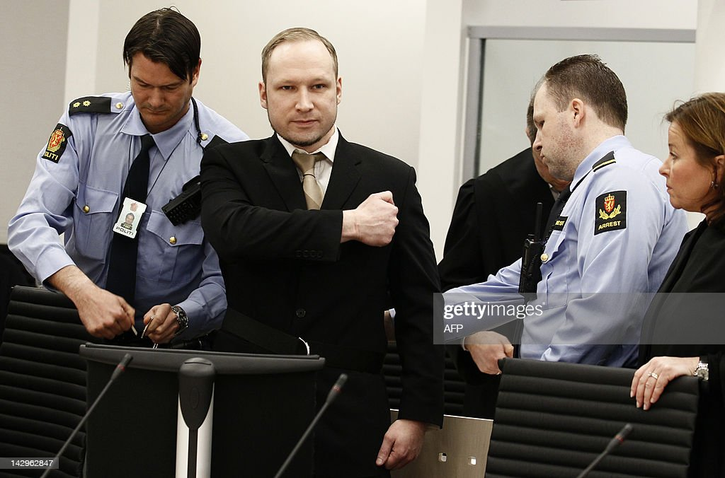 Rightwing extremist Anders Behring Breivik, who killed 77 people in twin attacks in Norway last year, makes a farright salute as he enters court in Oslo on April 16, 2012, for his trial which begins today. Wearing a black suit and with his blond hair shortly cropped, police ushered him to his seat at the front of the courtroom, under the gaze of survivors and family members of those he killed and hundreds of journalists from around the world. JUNGE