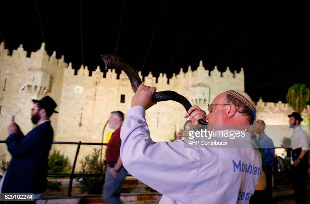 A rightwing Israeli man blows a Shofar a Jewish holy horn during a march next to Damascus gate on July 31 2017 to mark Tisha B'Av fasting and...
