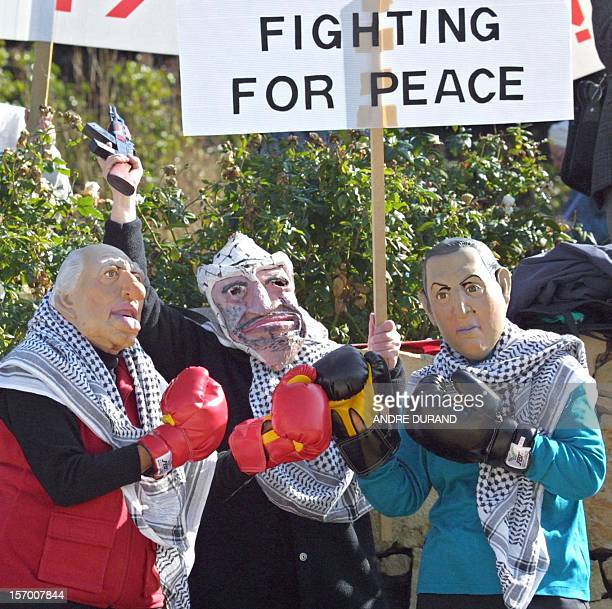 Rightwing Israelis wearing masks of Israeli caretaker Prime Minister Ehud Barak Palestinian Authority President Yasser Arafat and former Israeli...