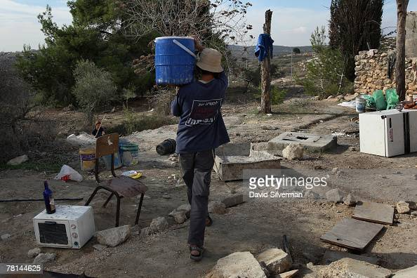 A rightwing Jewish youth carries water as settlers establish themselves in an abandoned Arab house where they are building their new unauthorised...